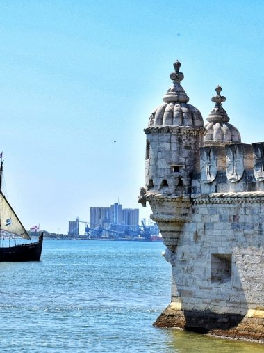 A sail ship cruises by Belem Tower in Portugal